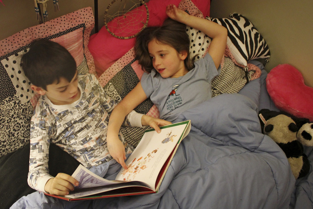 niños-cama-libro