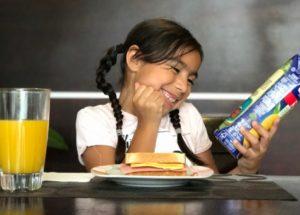 niña-lectura-jugo-desayuno
